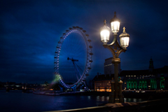 lamp post on westminster bridge with view to the london eye, night